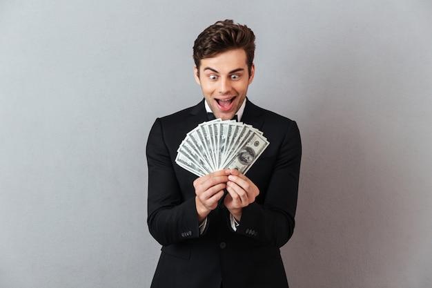 Mężczyzna krzyczy w oficjalnym garniturze gospodarstwa pieniądze.