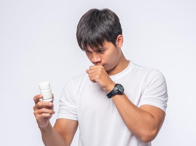 Mężczyzna, który jest chory i nosi butelkę z lekarstwem.