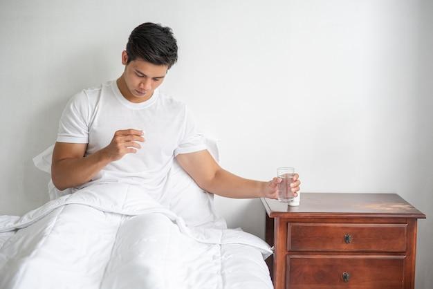 Mężczyzna, który źle się czuje na kanapie i ma zamiar zażyć antybiotyki.