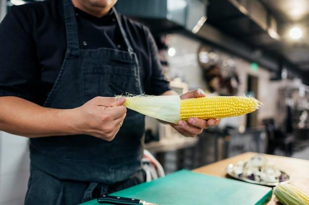 Mężczyzna kucharz czyszczenia kolby kukurydzy