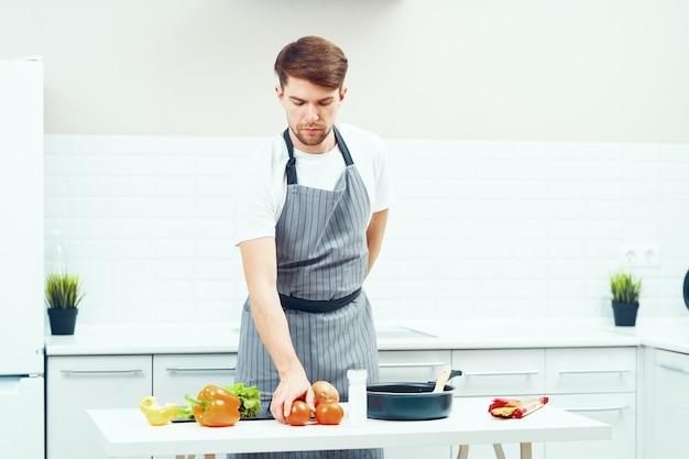 Mężczyzna kucharz gotuje w kuchni, zdrowe domowe jedzenie