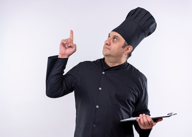 Mężczyzna kucharz kucharz ubrany w czarny mundur i kapelusz kucharz trzymając schowek pointng z palcem stojącym na białym tle