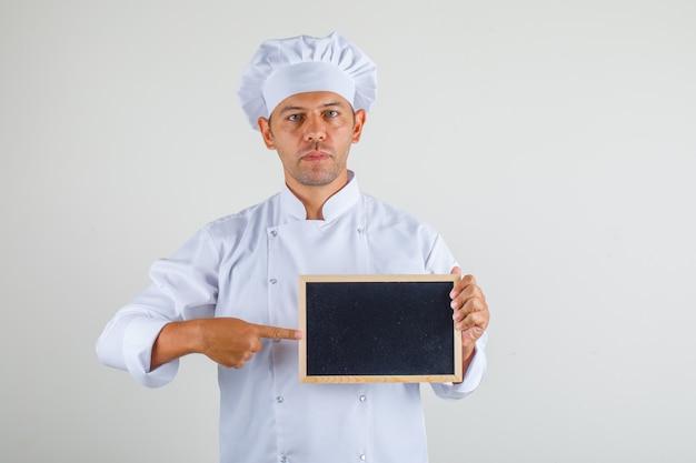Mężczyzna kucharz kucharz wskazując palcem na tablicy w kapeluszu i mundurze