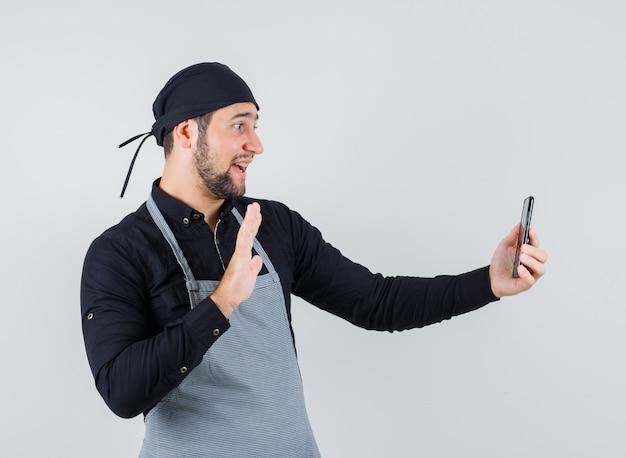Mężczyzna kucharz macha ręką podczas robienia selfie w koszuli, fartuchu i patrząc wesoło, widok z przodu.