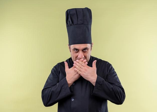 Mężczyzna kucharz na sobie czarny mundur i kapelusz kucharz patrząc na kamery uśmiechnięty chytrze zakrywając usta rękami stojącymi na zielonym tle