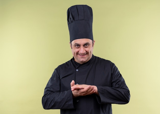 Mężczyzna kucharz na sobie czarny mundur i kapelusz kucharz patrząc na kamery z chytrym uśmiechem trzymając się za ręce razem stojąc na zielonym tle