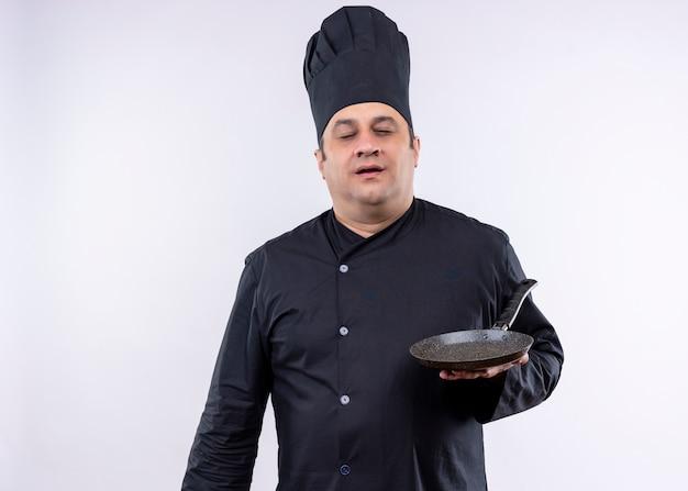 Mężczyzna kucharz na sobie czarny mundur i kapelusz kucharz trzyma patelnię z zamkniętymi oczami stojąc na białym tle