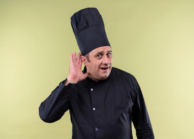 Mężczyzna kucharz na sobie czarny mundur i kapelusz kucharz, trzymając rękę przy uchu, próbując słuchać rozmowy kogoś stojącego na zielonym tle