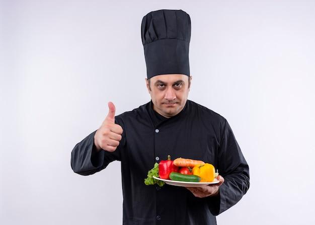 Mężczyzna kucharz na sobie czarny mundur i kapelusz kucharz trzymając talerz ze świeżymi warzywami pokazując kciuk do góry stojących na białym tle