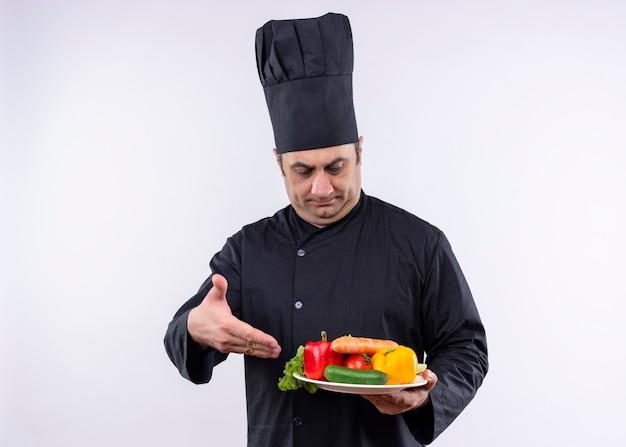 Mężczyzna kucharz na sobie czarny mundur i kapelusz kucharz trzymając talerz ze świeżymi warzywami, prezentując ramieniem ręki stojącej na białym tle