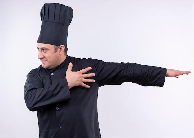 Mężczyzna kucharz na sobie czarny mundur i kapelusz kucharza patrząc na bok, wskazując ręką z boku stojącego na białym tle