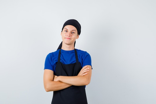 Mężczyzna kucharz nastolatek z rękami skrzyżowanymi w koszulce, fartuchu i wyglądający na zadowolonego. przedni widok.