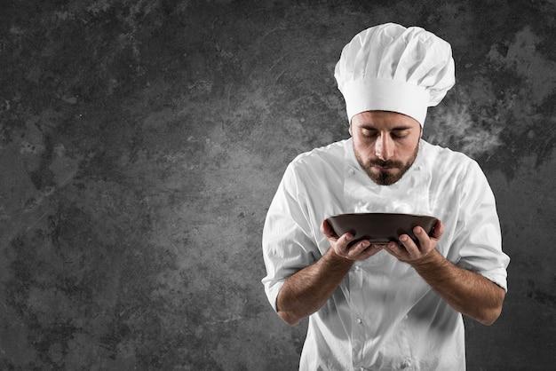 Mężczyzna kucharz pachnący aromatem swojej potrawy
