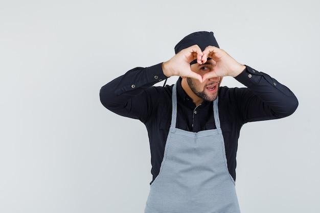 Mężczyzna kucharz pokazuje gest serca w koszuli, fartuchu i patrząc wesoło, widok z przodu.
