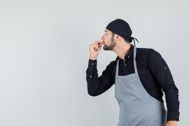 Mężczyzna kucharz pokazuje smaczny gest w koszuli, fartuchu i wygląda zachwycony, widok z przodu.