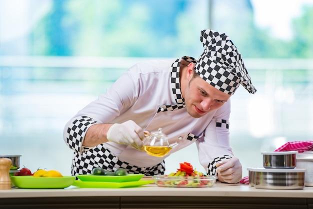 Mężczyzna kucharz przygotowuje jedzenie w kuchni