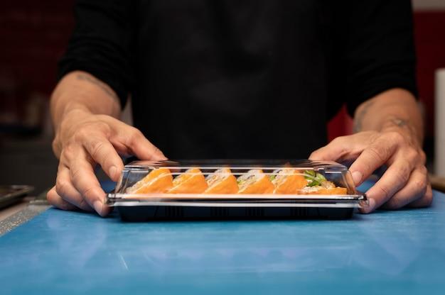 Mężczyzna kucharz przygotowuje zamówienie sushi na wynos