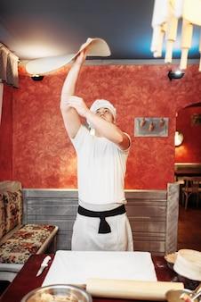 Mężczyzna kucharz robi ciasto w kuchni