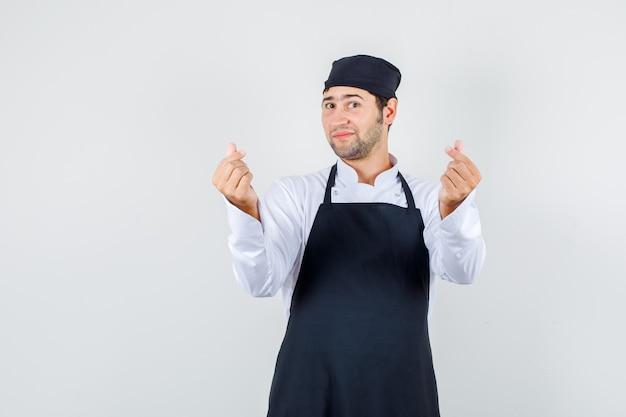 Mężczyzna kucharz robi koreański gest miłości w mundurze, fartuchu i wygląda optymistycznie, widok z przodu.