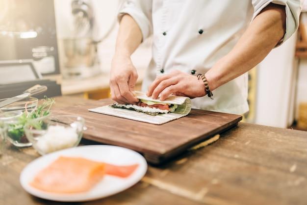 Mężczyzna kucharz robi owoce morza, kuchnia azjatycka