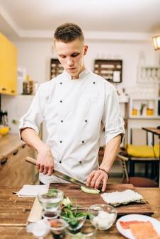 Mężczyzna kucharz robi sushi w kuchni. tradycyjne japońskie jedzenie, proces przygotowania, owoce morza