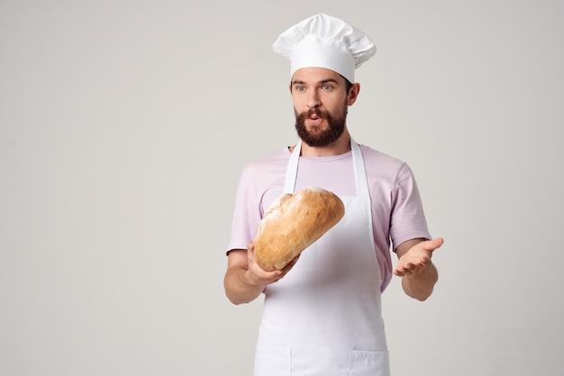 Mężczyzna kucharz trzyma chleb w jego rękach gotowanie profesjonalny piekarz. zdjęcie wysokiej jakości