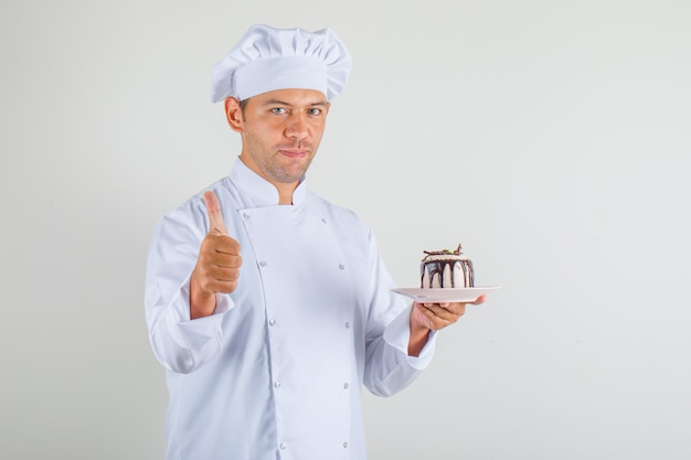 Mężczyzna kucharz trzyma ciasto i pokazuje kciuk w górę w kapeluszu i mundurze