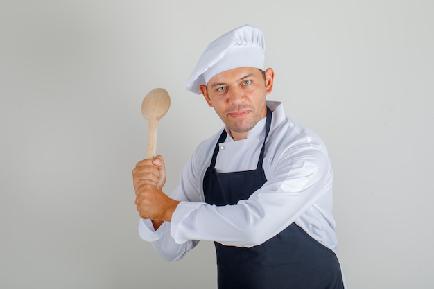 Mężczyzna kucharz trzyma drewnianą łyżkę w kapeluszu, fartuchu i mundurze