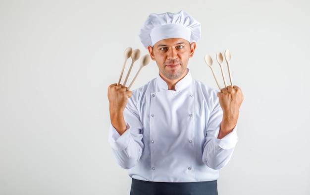 Mężczyzna kucharz trzyma drewniane łyżki i uśmiecha się w mundurze, fartuchu i kapeluszu i wygląda pewnie