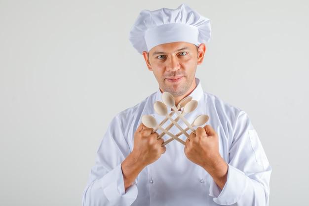 Mężczyzna kucharz trzyma drewniane łyżki i uśmiecha się w mundurze i kapeluszu i wygląda pewnie