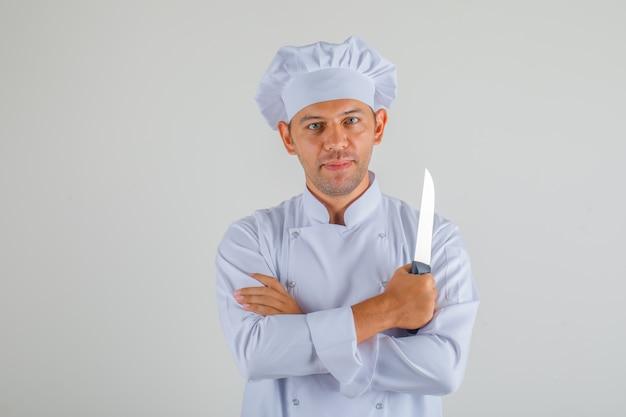 Mężczyzna kucharz trzyma nóż ze skrzyżowanymi rękami w mundurze i kapeluszu i wygląda pewnie