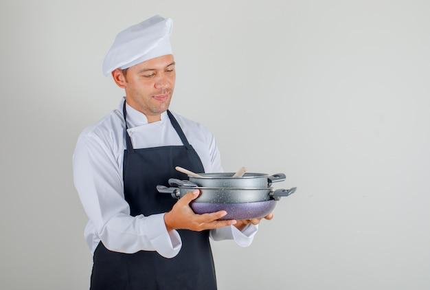 Mężczyzna kucharz trzyma patelnie z drewnianymi naczyniami w kapeluszu, fartuchu i mundurze