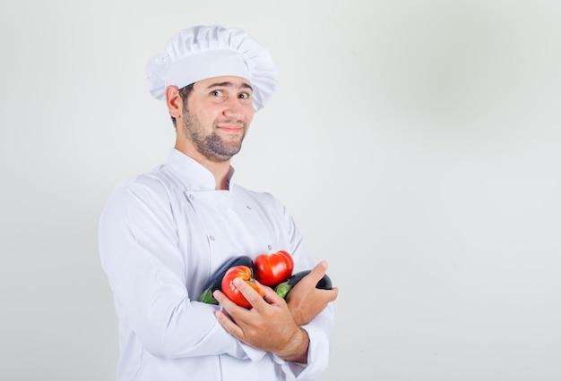 Mężczyzna kucharz trzyma pomidory i bakłażan w białym mundurze