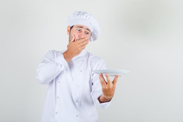 Mężczyzna kucharz trzyma talerz z ręką na głowie w białym mundurze i wygląda na zaskoczonego