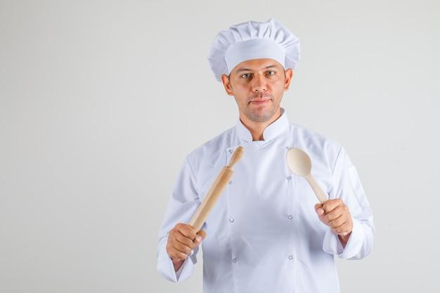 Mężczyzna kucharz trzyma wałek do ciasta i drewnianą łyżką w kapeluszu i mundurze