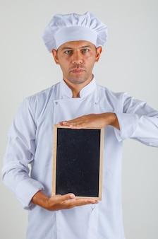 Mężczyzna kucharz trzymając tablicę i patrząc na kamery w kapeluszu i mundurze