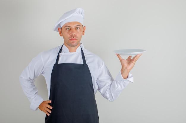 Mężczyzna kucharz trzymając talerz i kładąc rękę na talii w kapeluszu, fartuchu i mundurze