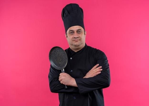 Mężczyzna kucharz ubrany w czarny mundur i kapelusz kucharz trzyma patelnię patrząc na kamery z pewnym siebie wyrazem twarzy stojącej na różowym tle