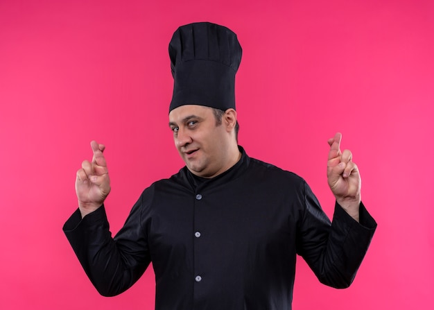 Mężczyzna kucharz ubrany w czarny mundur i kapelusz kucharza czyniąc pożądanym życzeniem skrzyżowanie palców stojących na różowym tle