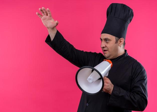 Mężczyzna kucharz ubrany w czarny mundur i kapelusz kucharza krzyczy do megafonu podnosząc rękę patrząc na bok stojąc na różowym tle