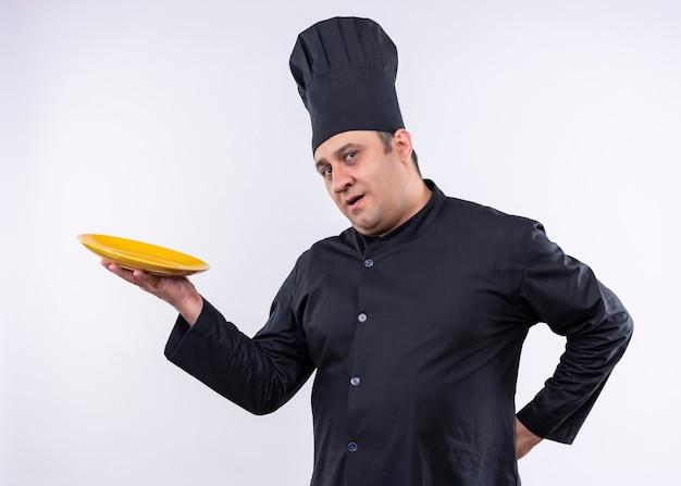 Mężczyzna kucharz ubrany w czarny mundur i kapelusz kucharza, pokazując talerz patrząc pewnie stojąc na białym tle