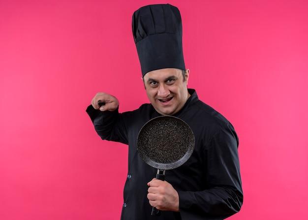 Mężczyzna kucharz ubrany w czarny mundur i kapelusz kucharza trzyma patelnię grożącą nożem patrząc na kamery z uśmiechem na twarzy stojącej na różowym tle