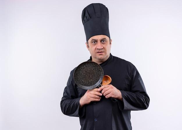 Mężczyzna kucharz ubrany w czarny mundur i kapelusz kucharza trzymając patelnię i drewnianą łyżkę patrząc na kamery zdezorientowany i bardzo niespokojny stojąc na białym tle