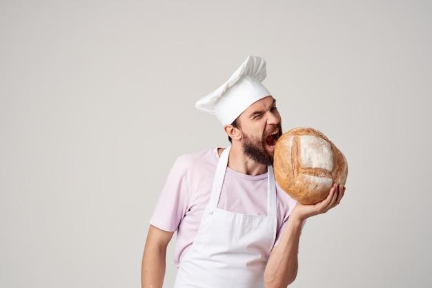 Mężczyzna kucharz w białym fartuchu co piekarz chleba. zdjęcie wysokiej jakości
