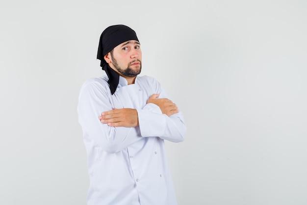 Mężczyzna kucharz w białym mundurze przytula się i wygląda skromnie, widok z przodu.