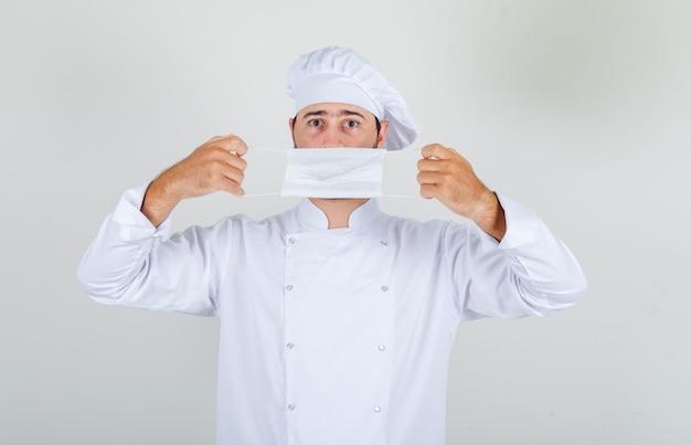 Mężczyzna kucharz w białym mundurze, trzymając maskę medyczną na ustach