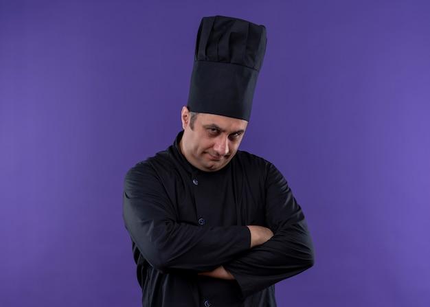 Mężczyzna kucharz w czarnym mundurze i kapeluszu kucharza patrząc na kamerę z marszczoną twarzą z sceptycznym wyrazem twarzy ze skrzyżowanymi rękami na piersi stojącej na fioletowym tle