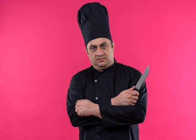 Mężczyzna kucharz w czarnym mundurze i kapeluszu kucharza trzyma nóż kuchenny ze skrzyżowanymi rękami patrząc na kamerę z twarzą seriouis stojącą na różowym tle