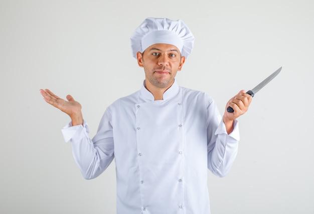 Mężczyzna kucharz w kapeluszu i mundurze trzyma nóż i wygląda na zdezorientowanego
