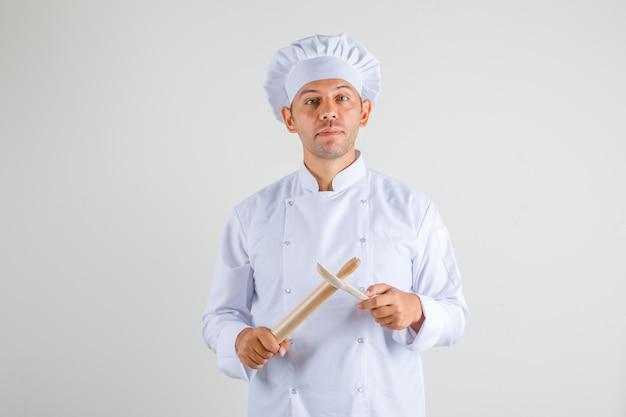 Mężczyzna kucharz w kapeluszu i mundurze trzymając wałek do ciasta i drewnianą łyżką
